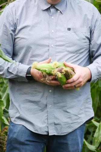 Photo of farmer with corn in hands